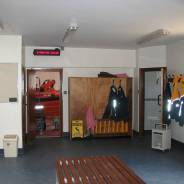 The view from the muster room into the boathall, with the lifeboat clearly visible. The red text screen over the door is part of the COACS paging syste