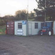 "The ""ops room"" and store - portakabin and 20' container. Also shown is ""T-575 Terence the Tractor"" used for launch & recovery every 2 weeks to scrub the hull."